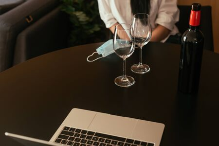 cropped view of woman sitting at table near wine glasses, bottle, medical mask and laptop