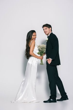full length view of smiling bride groom holding hand in pocket and looking away near african american bride looking at camera on white background