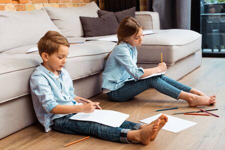 cute siblings sitting on floor and drawing in living room Stockfoto