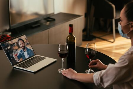 selective focus of young woman in medical mask having video chat with boyfriend near glasses and bottle of red wine