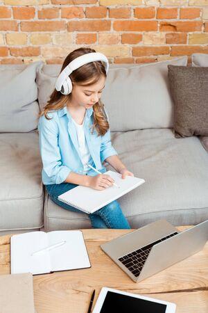 cute kid in headphones writing in notebook near gadgets