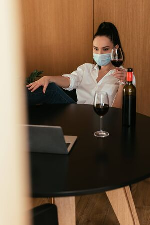 young woman in protective mask holding glass of red wine during video chat on laptop