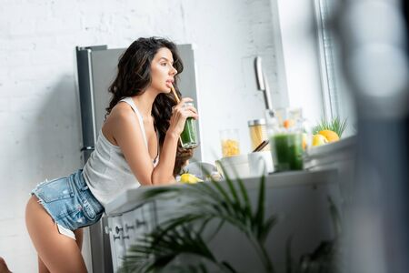 Selective focus of sensual woman drinking smoothie in kitchen