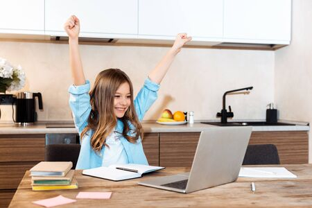 selective focus of happy kid with hands above head looking at laptop while e-learning at home