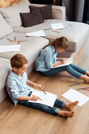 cute brother and sister sitting on floor and drawing in living room Banque d'images