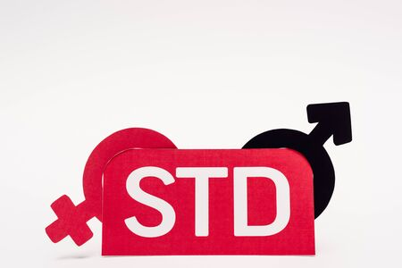 gender symbols near paper with std lettering on white