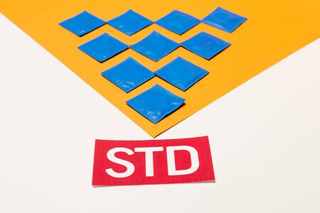 packs with condoms on orange surface near std lettering isolated on white