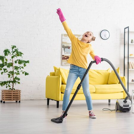 Cute child with closed eyes and outstretched hand singing with vacuum cleaner in living room
