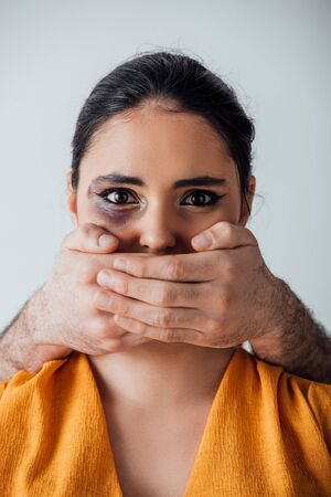 Male hands covering mouth to indian woman with bruise isolated on grey Banque d'images