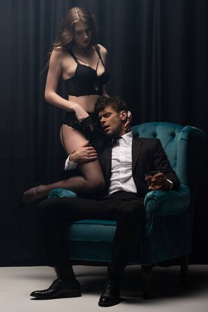 handsome man in suit sitting in armchair, holding glass of whiskey and touching attractive woman in lingerie on black Foto de archivo