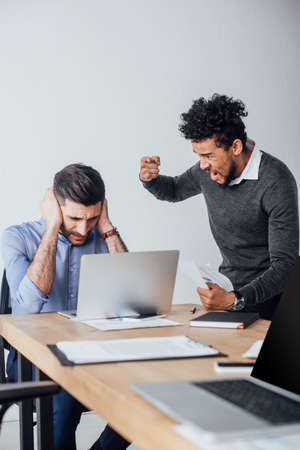 Selective focus of angry african american businessman quarreling at colleague covering ears in office Stock Photo