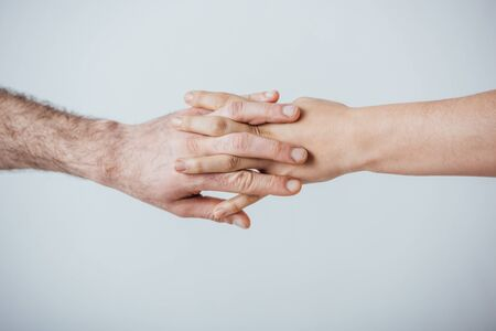 Cropped view of man and woman holding hands isolated on grey