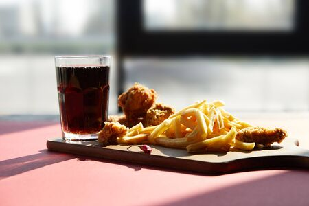 crispy deep fried chicken and french fries served on wooden cutting board with soda in sunlight near window