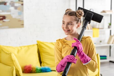 Child with vacuum cleaner smiling and looking away in living room