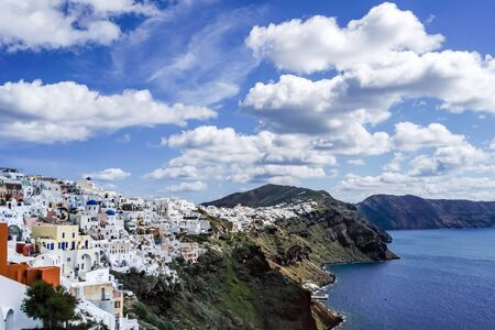 white houses near tranquil sea against blue sky with clouds in greece