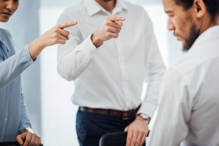 Selective focus of business people pointing with fingers at african american colleague