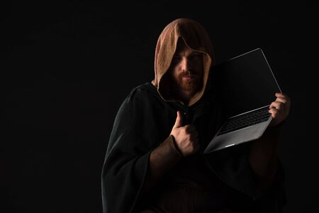 medieval Scottish redhead man in mantel holding laptop and showing thumb up in dark isolated on black Stock fotó