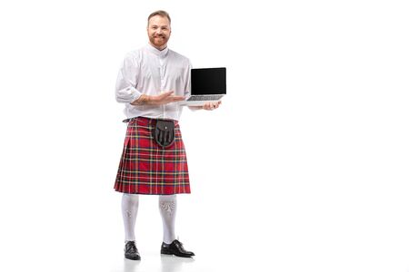 smiling Scottish redhead man in red kilt holding laptop with blank screen on white background
