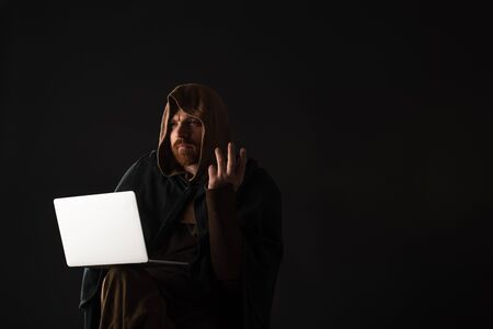 confused medieval Scottish man in mantel using laptop in dark isolated on black