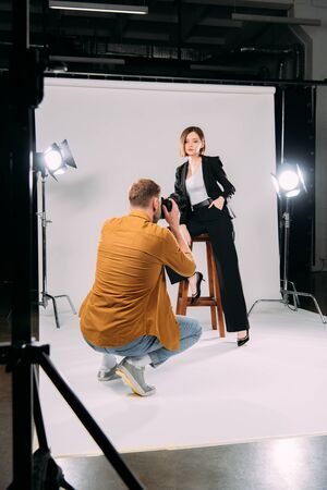 Selective focus of photographer working with stylish model on chair in photo studio