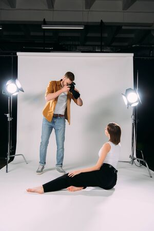 Photographer using digital camera while working with model in photo studio