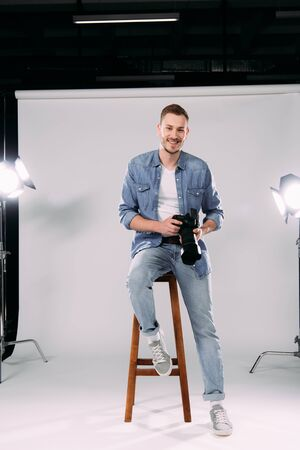Handsome photographer smiling at camera while holding digital camera on chair in photo studio