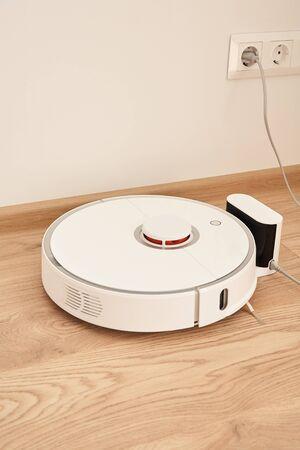 modern robotic vacuum cleaner near power sockets on wall 版權商用圖片