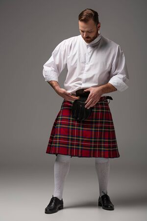 Scottish redhead man in red kilt putting gold coins in belt bag on grey background