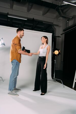 Side view of smiling model shaking hands with photographer in photo studio