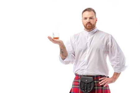 Scottish redhead man in red kilt with whiskey in glass on hand isolated on white