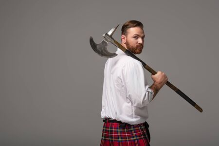 Scottish redhead man in red kilt with battle axe on grey background