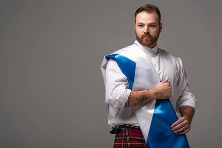 serious Scottish redhead man in red kilt with flag of Scotland on grey background