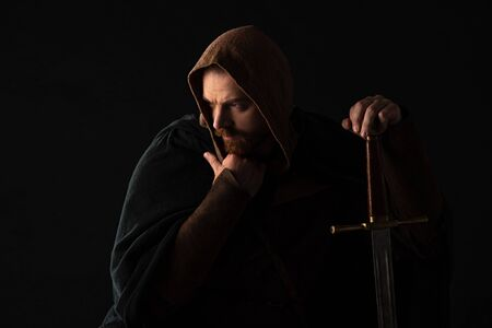 frowning medieval Scottish man in mantel with sword in dark isolated on black