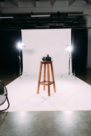 Digital camera on wooden chair in photo studio
