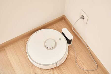 top view of modern robotic vacuum cleaner near power socket on wall