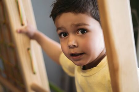 selective focus of adorable boy climbing on ladder in home gym