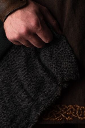 hand of medieval Scottish adult man in brown clothing