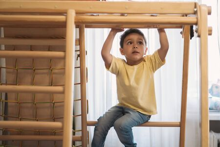 adorablle boy exercising in home gym while sitting on ladder Фото со стока