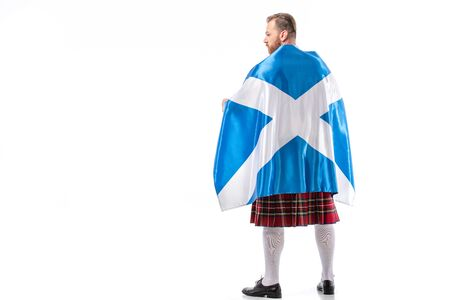 back view of Scottish redhead man in red kilt with flag of Scotland on white background