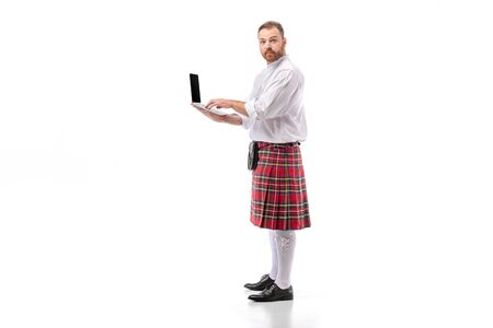 Scottish redhead man in red kilt holding laptop on white background