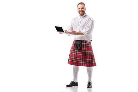 smiling Scottish redhead man in red kilt with digital tablet on white background