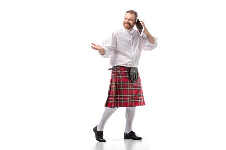 smiling Scottish redhead man in red kilt talking on digital tablet on white background