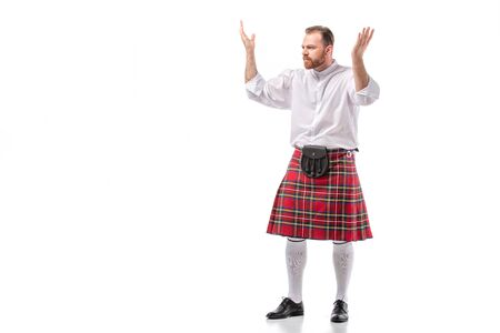 Scottish redhead bearded man in red tartan kilt showing shrug gesture on white background
