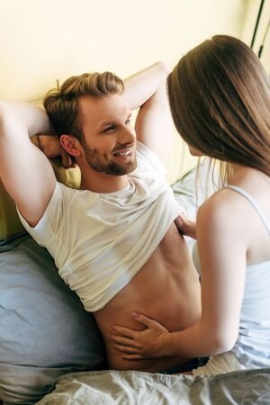 selective focus of cheerful man looking at young woman in bedroom