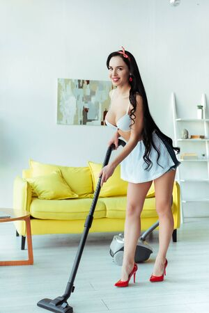 Sensual smiling woman in apron cleaning floor with vacuum cleaner in living room