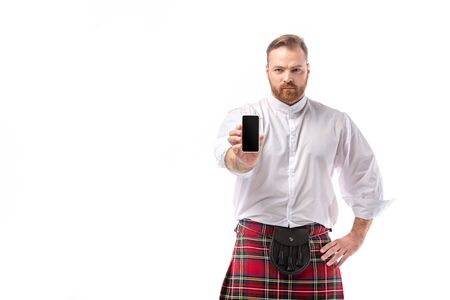 serious Scottish redhead man in red kilt presenting smartphone with blank screen isolated on white