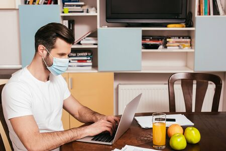 Side view of man in medical mask working on laptop near orange juice and fruits on table