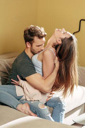 passionate man kissing beautiful girl in living room