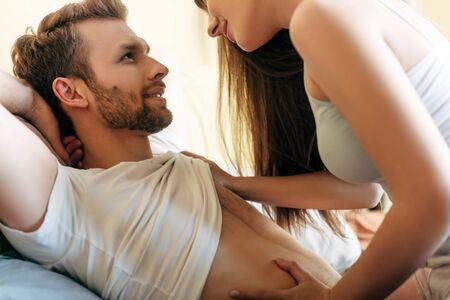 cheerful woman touching muscular man in bedroom Standard-Bild