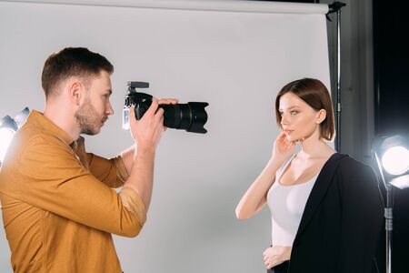 Handsome photographer working with beautiful young model in photo studio